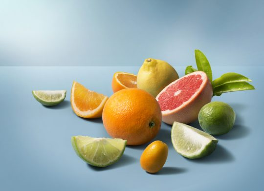 A group of mix citrus fruits on clean blue background. Studio shot image.