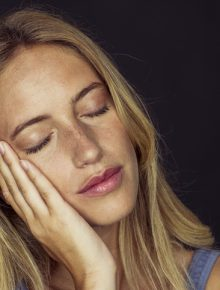 Young woman resting cheek on hand, eyes closed, portrait